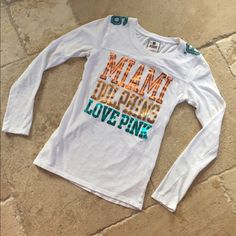 PINK by Victoria's Secret Miami Dolphins T Shirt PINK BY Victoria's Secret Miami Dolphins T-Shirt. Size S. Long sleeve. Design on front an '66 on shoulders. 100% cotton. VERY GOOD CONDITION!! No trades. PINK Victoria's Secret Tops Tees - Long Sleeve