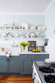 This dark, run-down kitchen was transformed into an inviting space full of country charm. The lower cabinets are painted dark gray-blue and open shelving shows off a collection of souvenir plates alongside cake stands, enamelware, and sweet little pie birds.
