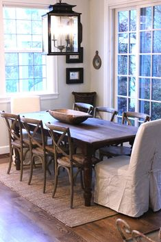 Casual dining room with large scale lantern, cross-back chairs & linen slips on head chairs - Jill Hinson's home