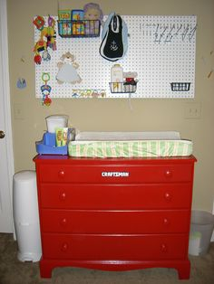"""Tool themed boy's room - peg board for storage and a """"Craftsman"""" dresser/changing table.  Bought the Craftsman plate online and glued it to the dresser, which we painted red."""