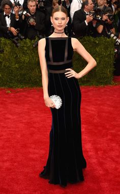 2015 Met Gala: Behati Prinsloo wore a black velvet Tommy Hilfiger sleeveless gown with sheer pieces on the bodice. Velvet is not the fabric for spring but Tommy did a beautiful job using velvet for spring in a beautiful way. The dress fits Behati like a glove!