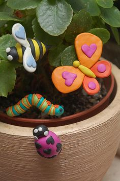 Creating love bugs from colorful clay to decorate garden pots is a great family gardening craft.