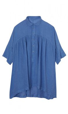 FIRA BLOUSE. Mid-blue linen blouse with buttoned through front and dipped hem. The yoke is gently gathered with a simple rounded collar.