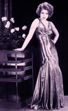 CLARA BOW the 'IT' girl & silent screen star, wears a long bias-cut silver lamé evening dress for her role in No Limit (1921) Lamé was a popular glamorous choice for the evening, & for film costumes. From Decades of Fashion : The Hulton Getty Collection by Harriet Worsley (2000) (please follow minkshmink on pinterest) #flapper #twenties #roaringtwenties #jazzage #glamour #clarabow #lamé