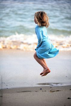 Girl jumping on the beach wearing blue dress  by Dina Giangregorio