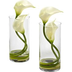 Create a lush tablescape or charming vignette with this lovely faux calla lily arrangement, featuring elegant blossoms nestled in a classic glass vase.