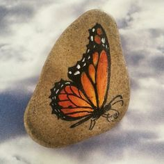 """Butterfly Brooch Painting on stone This gorgeous little brooch is made of a pale tan/grey river stone painted with a vibrant Monarch butterfly. It has a silver tone pin glued to the back. Signed in pencil on the back by the artist """" Odette"""". This beautiful piece was handpainted by artist Odette Acuna. This pin is in excellent condition.  From a smoke free home.  Offers welcome :) Artisan Jewelry Brooches"""