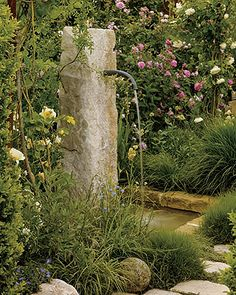 white and pink David Austin roses surrounding an antique stone column turned fountain.