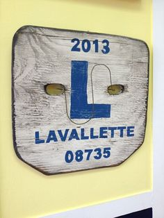 A wooden sign that looks like our Summer beach badge in Lavallette, NJ.