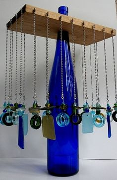 Necklace Hanger...Find a glass bottle you would like to use with a long neck; cut a hole in the center of a piece of plywood; add screw-in hook around the edges of the plywood; hang necklaces!