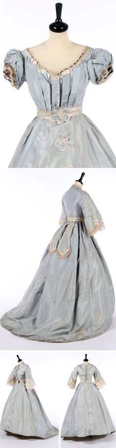 Dress with day & evening bodices, ca. 1868. Pale blue silk. Evening bodice (top photo), with puffed sleeves, trimmed with bobbin lace & black velvet ribbon. Day bodice (all other photos) with pearlized buttons. Long oval skirt trimmed with satin-edged florets; matching belt. Kerry Taylor Auctions