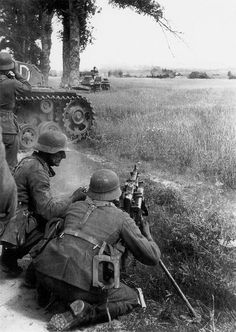 """German machine-gun crew firing a MG-34. Summer 1941, Army Group """"North"""". In the background, armor is ranging to fire. pic.twitter.com/zKWcvOFOcM"""