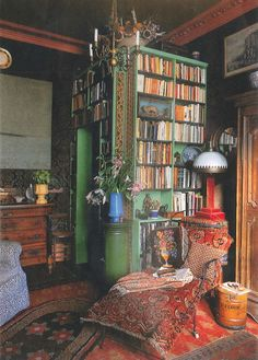 Bohemian library, floor-to-ceiling books, green, carpet on chair, most awesome bureau ever. Red lamp is happening -- lamp-ening.