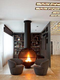 cheminée contemporaine, un foyer rond fermé et une bibliothèque moderne