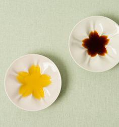テーブルに華を添える桜の模様が浮かぶ九谷焼の紅白小皿
