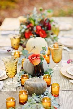 Fall table centerpiece with orange roses, eucalyptus, white and blue pumpkins. Golden goblets