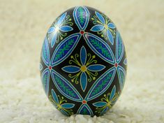 An fun little intertwining circle egg, featuring blue and yellow lilies nestled among intertwining circles which make interesting oval patterns. Inside the ovals are pine branches. This egg is a jumbo egg, and was made using traditional methods and techniques. The colors used in Carved Eggs, Easter Egg Designs, Ukrainian Easter Eggs, Painted Shells, Egg Art, Ancient Symbols, Easter Cookies, Chicken Eggs, Egg Decorating