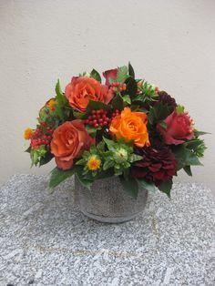 autumnal flower arrangement of orange roses, red dahlias and viburnum berries  by Judith Blacklock