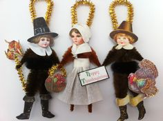 Set of three vintage style chenille bump ornaments...THANKSGIVING PILGRIM CHILDREN...three different pilgrims; two boys and one girl...one boy in dark brown chenille with a black chenille waistband holding a bushel of corn on a gold tinsel stem...girl in brown chenille with a white crepe paper skirt holding a basket of fruit with a gold tinsel handle in one hand and holding a Happy Thanksgiving banner in the other hand...other boy is in dark brown chenille with a black chenille waistband…