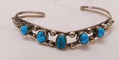 """445: Navajo S.S. & Turquoise Cuff, circa 1970s. Made of sterling silver and turquoise, the item measures 2 1/4"""" x 2"""" x 1/4"""", and weighs 8.9 grams. Inside measurement of 5.25"""". Navajo, Arizona. Silver leaf and silver bead design with 5 turquoise stones. Condition: Good, see images. Shipping: $12.50 w/insurance and signature. Turquoise Cuff, Turquoise Stone, Turquoise Bracelet, See Images, Silver Beads, Navajo, 1970s, Arizona"""