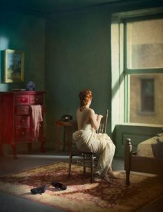 "Drawing inspiration from the paintings of Edward Hopper, Richard Tuschman's series ""Hopper Meditations""evokes the moody color palettes, cityscape backdrops, and solitary female characters that are signature elements in Hopper's paintings."