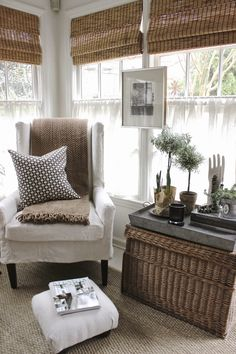 Picture hung on framing between windows, wicker trunks for storage and galvanized trays will prevent overwatering plants from being an issue