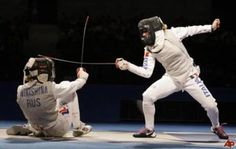 [ID: two foil fencers in a bout. The one on the right is lunging, and her opponent is parrying and falling over.]    Aida Shanaeva (left, is apparently wearing the wrong jacket) against Giovanna Trillini.