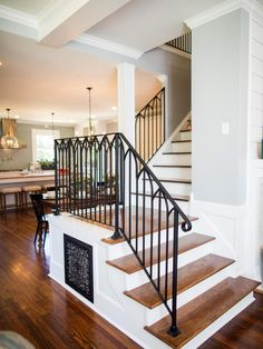 The stairwell is reconfigured with a more open design and enhanced with restored hardwood stairs. The iron railing echoes a design found in the home's vintage leaded-glass windows.