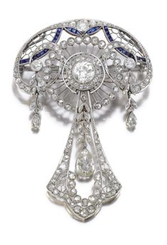 SAPPHIRE AND DIAMOND BROOCH/PENDANT, CIRCA 1915    Of open work foliate design highlighted with calibré-cut sapphires, centring on a circular-cut diamond within borders of cushion-shaped, circular-cut and rose diamonds, suspending three pear-shaped diamond drops, chain detachable, length approximately 480mm, fitted case.