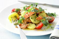This potato salad is given a gourmet make-over with the addition of smoked trout, cherry tomatoes and pea shoots.