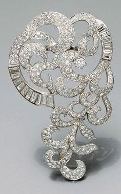 A magnificent platinum, white gold and diamond brooch, circa 1935. Designed as stylised scrolls and feathers set with pavé diamonds. #DiamondBrooches