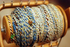 Use natural fibers, recycled from unwanted sweaters, and spin them together on a wheel or drop spindle with some thread, buttons, and beads to make your own unique art yarn!