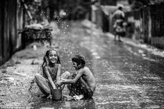 "Ata Mohammad Adnan won the Bangladesh category after taking this photograph of his neighbors in a slum. He said: ""I still remember how I ventured out in the neighborhood with my camera wrapped in protective cover and an umbrella as it started raining that afternoon. And as soon as I entered the next road beside my home, I saw these two girls playing with the rain water."" (2015 Sony World Photography National Awards)"