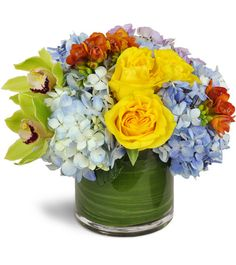 Bring all the colors of the clearest summer sky inside with this  uplifting floral gift featuring yellow roses, green cymbidium orchids,  hydrangea and freesias. A birthday, get-well sentiments, a