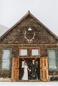 You don't necessarily have to step out in the snow to take beautiful wintry wedding photos. This couple stood in the doorway of their ceremony space for a striking portrait as the snow fell softly before them.