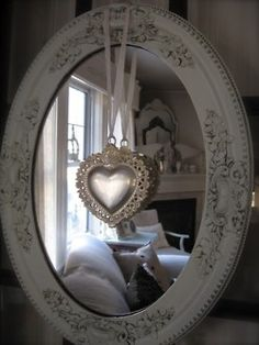 Vintage heart necklace on a ribbon...hanging on a vintage oval mirror...in a charming room!