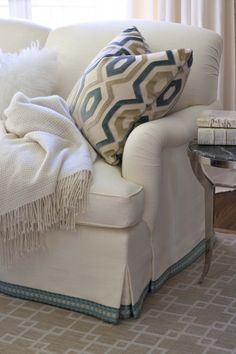 LOVE the way the fabrics on the pillows pick up all of the color in the room.  The trim is also a nice touch.