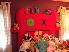 Queen size Ugly Doll Headboard. Made with plywood and felt.  Attached to bed frame and wall with two by fours and picture wire.