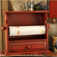 "Our Wood Paper Towel Holder combines practicality with fine workmanship. Designed to hang on wall or used on counter top, the functional drawer holds pencils & pens, key rings, or odds & ends. Red over Black painted finish with distressed edges.  13 1/2"" wide x 6 1/8"" deep x 12 3/4"" high."