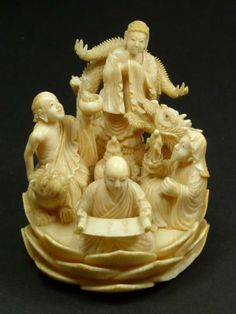 CHINESE CARVED IVORY STUDY OF FIGURES ON LOTUS
