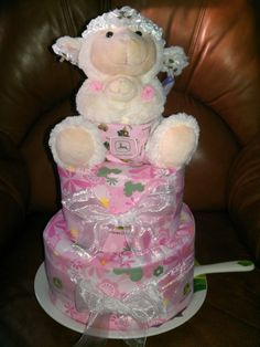 My niece is a country girl to the bone so here's the diaper cake I made for her baby shower.  Naturally, it's made primarily of diapers, but filled with misc. baby items.  It was covered with some pretty pink John Deere fabric and topped with an adorable mama and baby sheep (which is wrapped in a John Deere bib), all sitting on a China plate with a matching server.  I love diaper cakes!