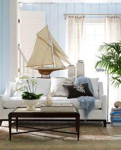 so much to love!  the rug, large boat, the lines of the sofa, the mix of chocolate, blue & white. . . .