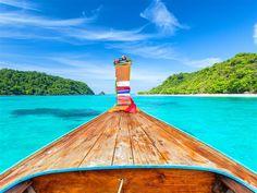 A long-tail boat gliding between idyllic Islands