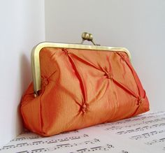 Pinched taffeta tangerine orange clutch bag in frame by toriska, $45.00
