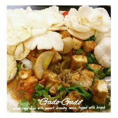"Gado-Gado Indonesian traditional salad from mixed of rich texture vegetables such as potato, beansprout, lettuce, tofu, boiled egg, with peanut dressing sauce, topped with ""emping"" and shrimp crackers"