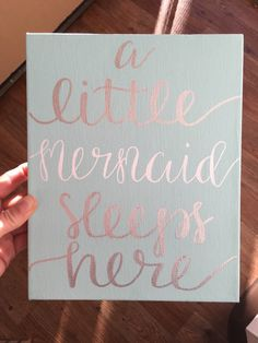 Canvas Sign In picture: a little mermaid sleeps here Hand lettered calligraphy text written in gold on light pink painted canvas sign 8 x 10 canvas sign Im here to create your favorite quotes on a canvas sign! If youd like your own custom quote, saying, etc.. in this 8 x 10 canvas sign, please follow these steps... 1. Purchase this listing 2. Choose your color text 3. Choose your background color 3. Write your saying in the notes section Please note that every sign is hand lettered and it...