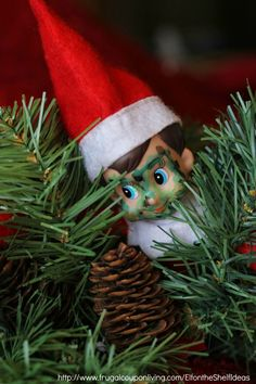 Elf on the Shelf Ideas – Elf is Camo in the Christmas Tree using dry earase markers plus daily Elf on the Shelf Ideas. Get FREE Printable Notes too!