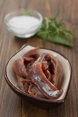 anchovies in dish on brown wooden background