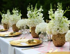 Katie Loves… an unexpected centerpiece idea, like these gilded pineapple vases from Pizzazzerie's baby shower. Paint the outside of a pineapple gold, dig out the fruit center and replace with floral foam, then add your flowers.