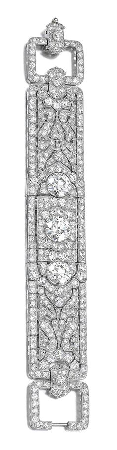 DIAMOND BRACELET, CIRCA 1925.  The wide band of Persian design, collet-set with three circular-cut diamonds within surrounds pierced and millegrain-set with circular- and single-cut stones, length approximately 180mm, associated case, R.W.Yeo Ltd.